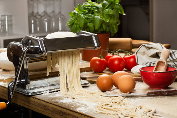 Pasta machine with noodles and ingredients on a wooden table