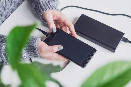 The girl is holding a phone connected to the power bank with a cable. Power bank charges a smartphone in women's hands. The discharged device