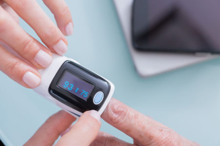 Doctor and patient using finger pulse oximeter